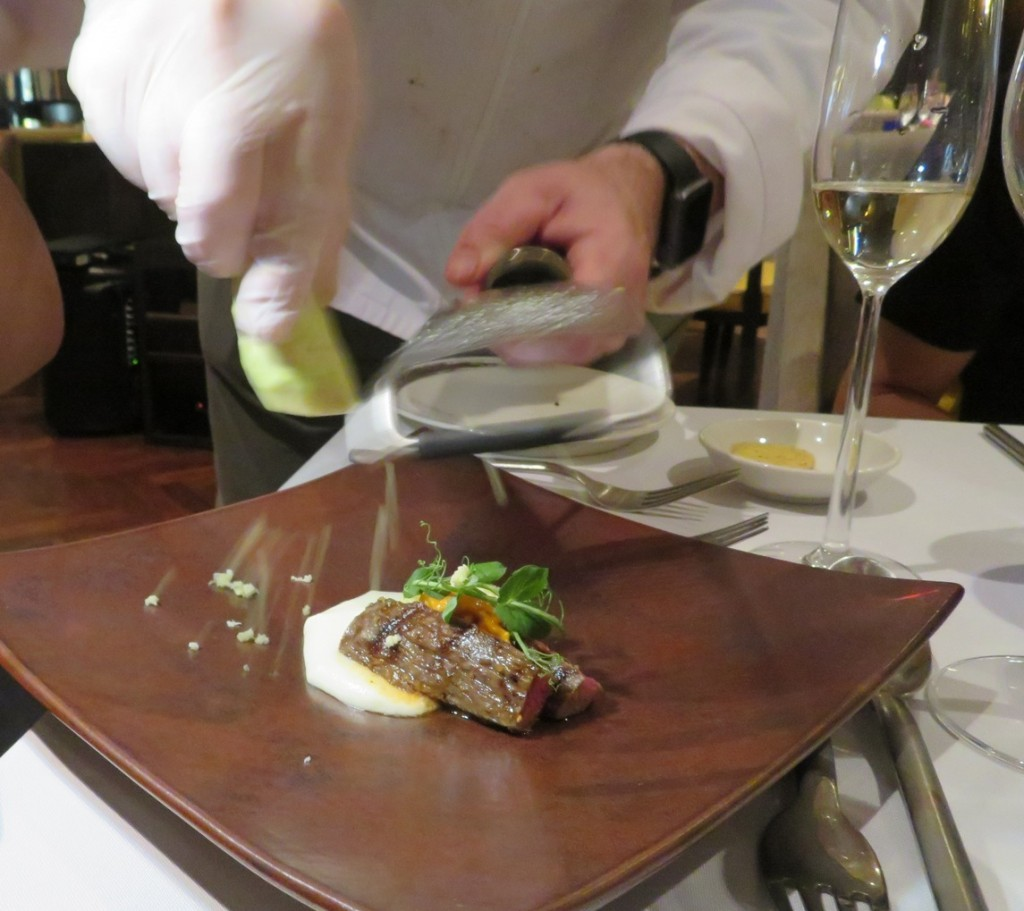 The chef shaving fresh wasabi over the  Wagyu Petit Tender Oer the Coals, Sea Urchin, Wasabi, Paris Mash