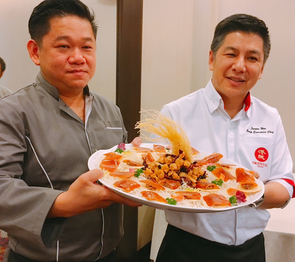 Chef James Ho, left, and Chef Justin Hor with their joint creation -- Roast Suckling Pig with Foie Gras Mousse. It's their centrepiece for their China & Nanyang feast